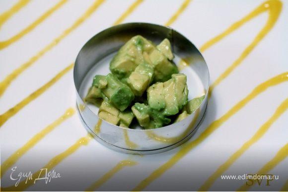 Поместив первое кольцо посередине тарелки , заполняем его 60 граммами сальсы из авокадо. Плотно упаковываем ее используя обратную сторону столовой ложки.