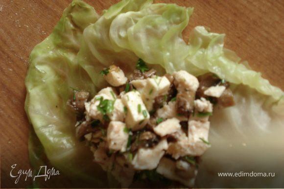 Выкладываем начинку на лист капусты, добавляем немного сметаны и заворачиваем конвертиком.
