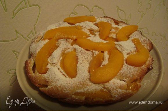 Оставшиеся персики нарезать дольками. Остывший пирог посыпать сахарной пудрой и украсить дольками. Вкусного вам чаепития!