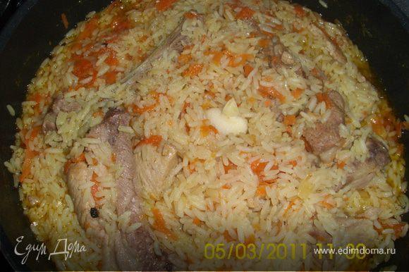 Лук нарезать кольцами, обжарить до золотистого цвета, морковь нашинковать, мясо ( у меня этот раз свинные рёбрышки) порезать, опустить в казан с луком, когда обжарится, опустить морковь, затем посолить, поперчить, залить кипятком (на высоту чайной ложки выше мяса) сделать медленный огонь и тушить 20 минут. Затем опускаем рис, разглаживаем, заливаем водой (на высоту пол чайной ложки), даём закипеть (крышку не закрывать). Когда рис разбухнет, огонь сделать медленный, рис перемешать, собрать горкой, воткнуть зубчики чеснока, плотно закрыть крышкой и на медленный огонь до готовности! Перед подачей чеснок вынуть и всё ещё раз хорошо перемешать.