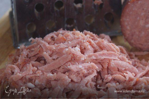 Натираем на крупной терке колбасу, отправляем в кастрюлю. Можно заменить колбасу на слабосоленую семгу, её необходимо мелко нарезать.