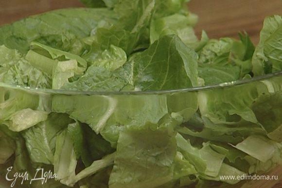 Листья салата порезать и полить заправкой.