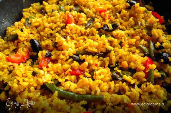 Отвариваем рис со специями. В это время на разогретой сковороде с оливковым маслом готовим стручковую фасоль, в конце готовки слегка обжариваем и добавляем порезанные сладкий перец и перец чили, кукурузу. Слегка обжариваем все ингредиенты. Добавляем приготовленный отдельно рис. Тщательно перемешиваем, прогреваем. Кладём порезанные пополам маслины, ещё раз мешаем. Даём постоять буквально минутку под крышкой и выключаем. Паэлья готова. Приятного аппетита! :)