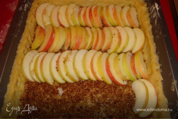 На получившееся из теста основание пирога высыпать пряно-ореховую смесь и разровнять по всей поверхности. Сверху красиво уложить яблочные дольки...