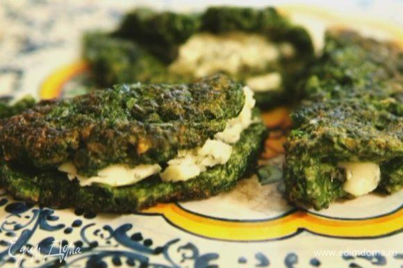 Положить на каждый блинчик немного голубого сыра, свернуть пополам и подавать.