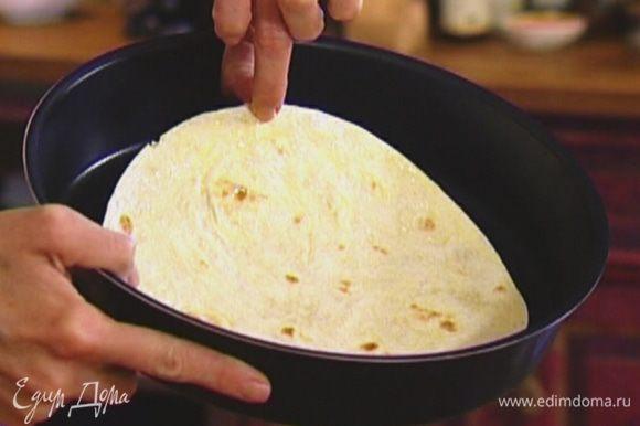 Тортилью выложить в форму, слегка смазать оливковым маслом и поместить на 7–10 минут в разогретую духовку.