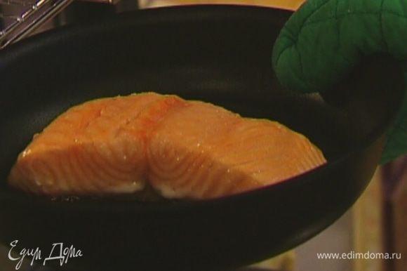 На сковороду, которую можно ставить в духовку, выложить семгу кожей вниз, поставить на небольшой огонь и жарить, пока рыба не посветлеет снизу, а затем отправить на 10–15 минут в разогретую духовку.
