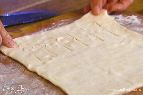 Размороженный пласт теста немного растянуть в стороны руками. Один край (до середины) нарезать полосками шириной 1,5–2 см.
