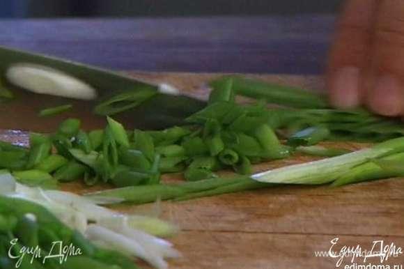 Зеленый лук нарезать наискосок и всыпать к картошке.