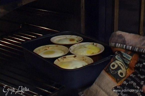 Поставить в глубокий противень формочки с яйцами и налить в него кипяток по верхний край формочек. Запекать в разогретой духовке 10-12 минут.