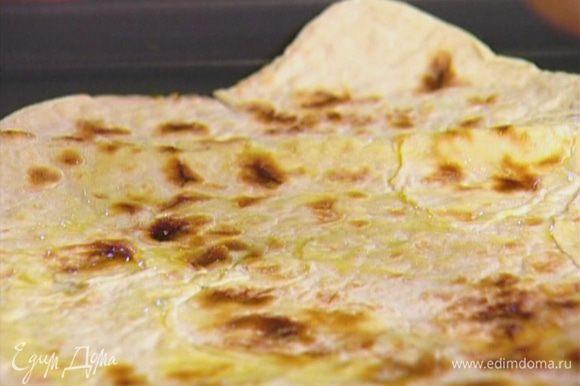 Лаваш выложить на противень, смазать оставшимся оливковым маслом и отправить в разогретую духовку на 2–3 минуты.