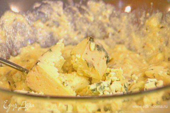 Влить растопленное масло с водой, добавить творог, яйцо, измельченный сыр и вымешать.