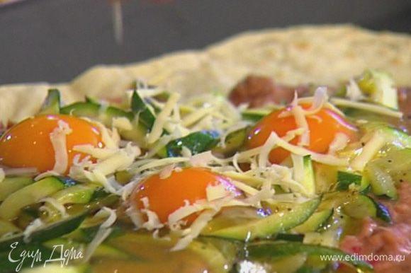 Сверху разбить яйца и посыпать натертым сыром.