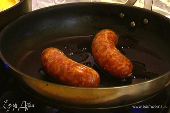 В другой сковороде разогреть оставшееся оливковое масло и обжаривать колбаски 6–8 минут, до готовности.