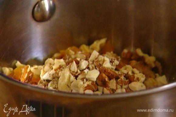 Все орехи слегка измельчить в ступке и соединить с курагой и клюквой.