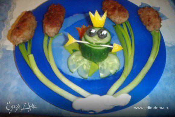 Сначала жарим обычные котлетки, только слегка продолговатые. Затем выкладываем их с зеленым луком. Потом из огурца, кожуры лимона и оливок делаем такую вот замечательную лягушку