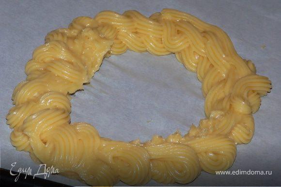 При помощи кондитерского мешка на деко, застеленное бумагой выдавить тесто в форме кольца (15-20см), посыпать миндальной стружкой.