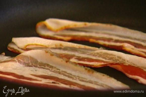 Бекон обжарить с двух сторон на сухой сковороде и выложить на бумажное полотенце, чтобы убрать излишки жира, затем поместить на нижнюю половинку булочки.