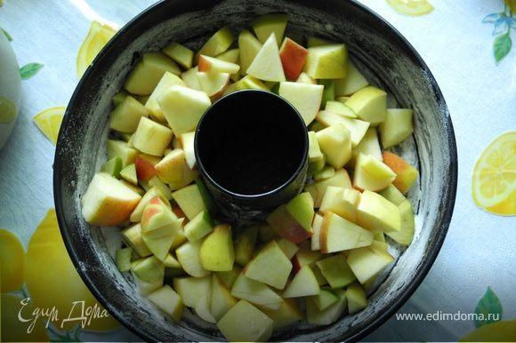 Форму смазать маслом, посыпать мукой и положить в нее нарезанные яблоки.