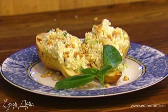 Наполнить половинки груш творожной начинкой, присыпать кедровыми орехами и украсить листьями базилика.