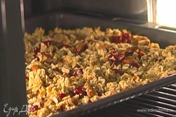 Противень с гранолой поместить в разогретую духовку, сразу же уменьшить температуру до 150°С и оставить на 10 минут.