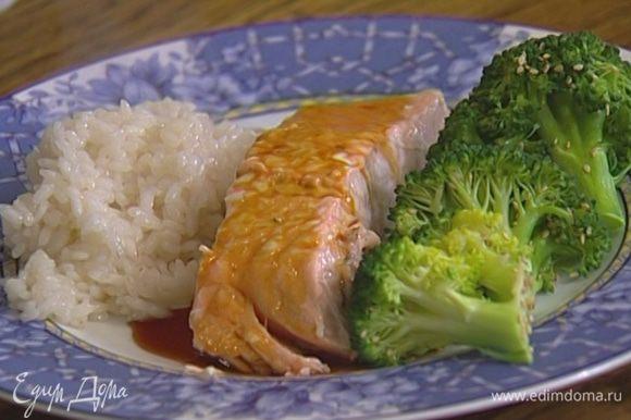 Выложить на тарелку рыбу, брокколи и рис. Полить все кунжутно-соевым соусом, посыпать оставшимся кунжутным семенем.