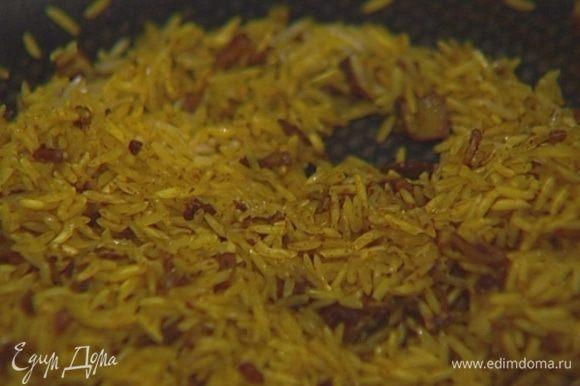 Всыпать рис, помешивая, обжаривать 1-2 минуты, затем влить горячий овощной бульон, закрыть крышкой и варить рис до готовности.