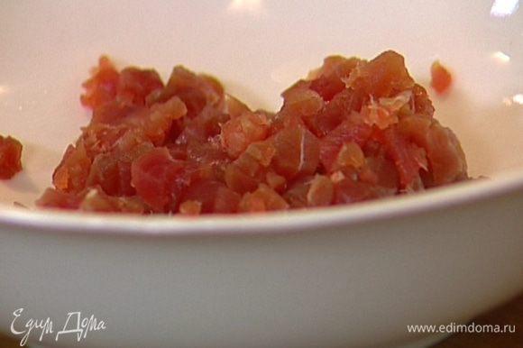 Тунца мелко порубить ножом, добавить желток, по щепотке соли и перца и все вымешать.
