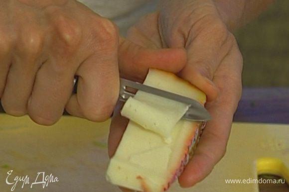 Сыр тонко нарезать с помощью ножа для чистки овощей.
