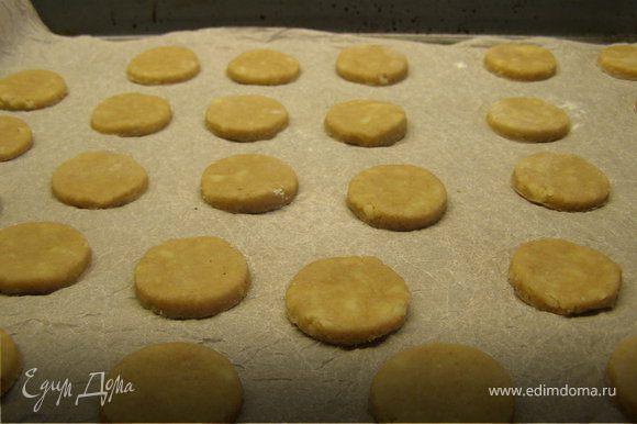 Достать тесто из холодильника. Раскатать в пласт и вырезать печенюшки. Разложить их на противне, выстеленном пекарской бумагой.