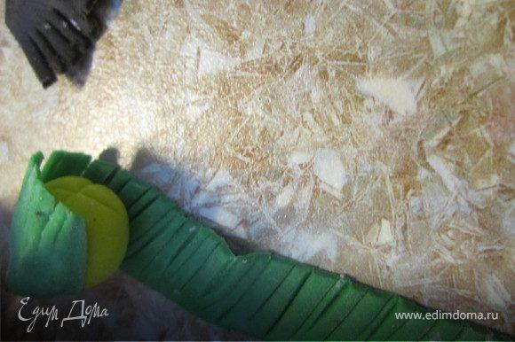 Края зеленой полоски смочить водой. Взять желтую серединку и завернуть в зеленую бахрому.