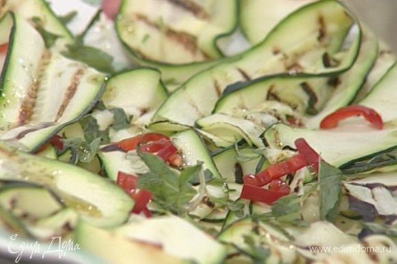Выложить цукини на большое блюдо, присыпать измельченным перцем чили и листьями мяты, полить заправкой.