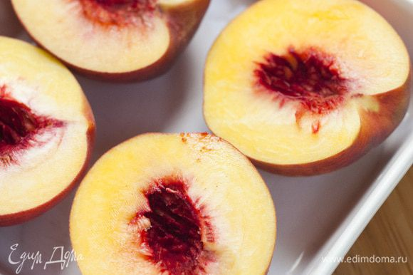 Персики разрезать пополам и, вынув косточки, уложить в керамическую посуду.