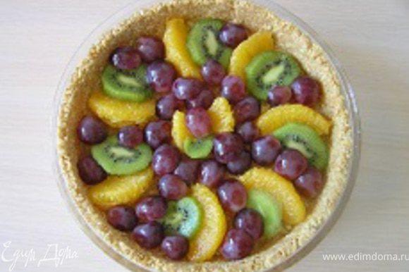 Сверху разложить кусочки фруктов, для этого апельсинные дольки освободить от пленок, киви нарезать кружочками, виноград на половинки.