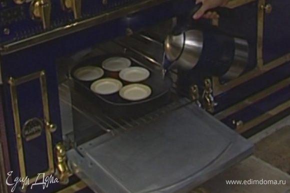 Поставить формочки с кремом в глубокий противень, наполненный горячей водой, и запекать в разогретой духовке 25–30 минут.