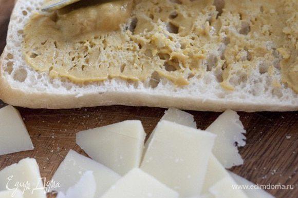 Хлеб надрезать сбоку, не прорезая до конца, затем раскрыть, сбрызнуть оливковым маслом и смазать горчицей, уложить на одну половину хлеба листья салата, мясо и сыр, накрыть второй половиной и разрезать чиабатту на 4 части.