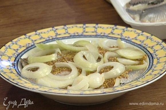 Равномерно выложить половину нарезанного лука на тарелку, сверху уложить всю селедку, намазать горчицей, полить уксусом и растительным маслом, накрыть оставшимся луком и поставить на некоторое время мариноваться.