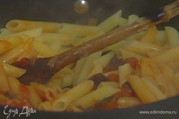 Выложить в сковороду к соусу макароны, фету, половину листьев базилика и все перемешать. Если получилось суховато, влить немного оставшейся после варки макарон воды и снова перемешать.