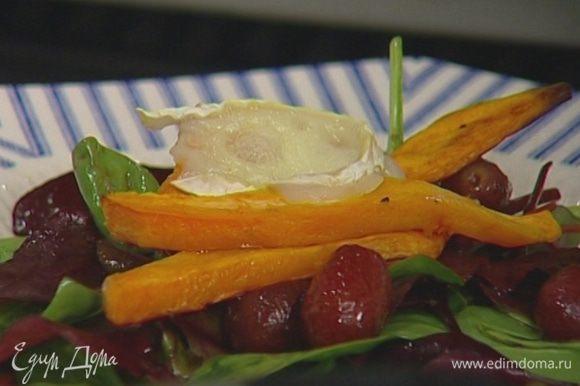 Выложить на большое блюдо листья салата, полить заправкой с каперсами и оливками, сверху разложить картофель и сыр, присыпать запеченным виноградом.
