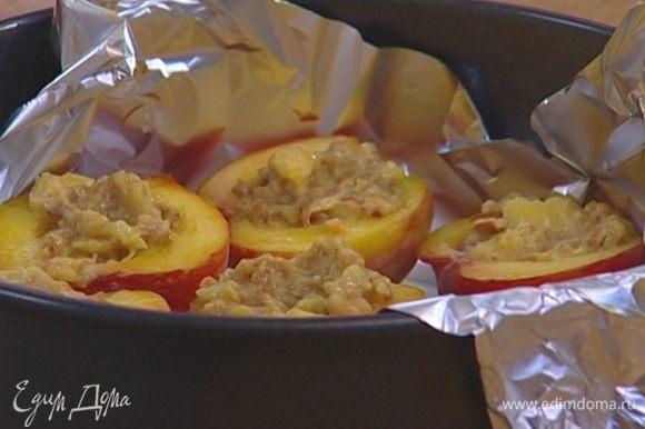 Выстелить фольгой глубокую форму для выпечки, уложить в нее половинки персиков и наполнить их начинкой.