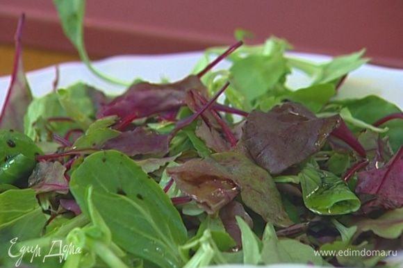 Листья салата выложить на большое блюдо, слегка сбрызнуть оливковым маслом и бальзамическим уксусом.