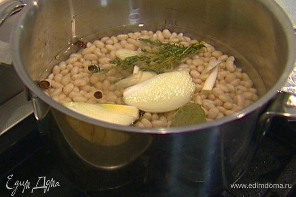 Фасоль замочить в воде на ночь, затем воду слить. Добавить в кастрюлю луковицу, чеснок, тимьян, лавровый лист. Залить все холодной водой и отваривать фасоль до готовности.