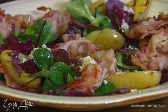 Разложить на блюде листья салата, присыпать оставшимися кубиками сыра, сверху выложить обжаренный картофель и бекон, полив каждый слой заправкой.