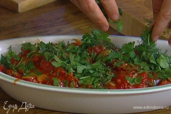 В глубокую форму, в которой можно будет подавать рыбу, уложить стейки, сверху полить томатным соусом, присыпать половиной укропа и петрушки.