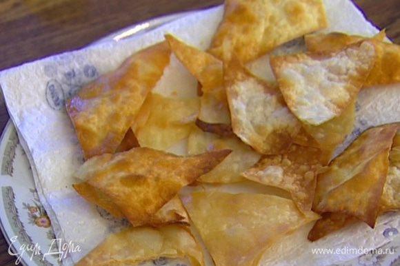 Разогреть в глубокой сковороде растительное масло, опускать в него кусочки лаваша и обжаривать, пока не получатся чипсы. Выложить на бумажное полотенце, чтобы избавиться от лишнего масла.