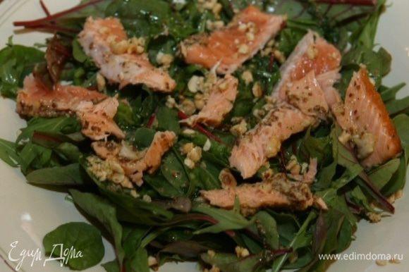 Выложить салат на большое блюдо, полить заправкой, присыпать половиной фундука, сверху уложить кусочки рыбы без кожи, присыпать оставшимися орехами и петрушкой.