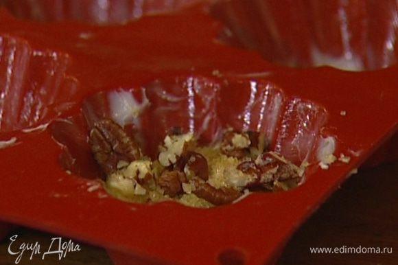 Смазать формочки для кексов оставшимся сливочным маслом. Выкладывать тесто и начинку из орехов слоями - слой орехов, затем слой теста, слой орехов и снова тесто.