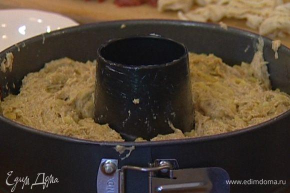 Смазать форму для выпечки растительным маслом, выложить в нее тесто, накрыть влажным полотенцем и оставить, чтобы тесто подошло.