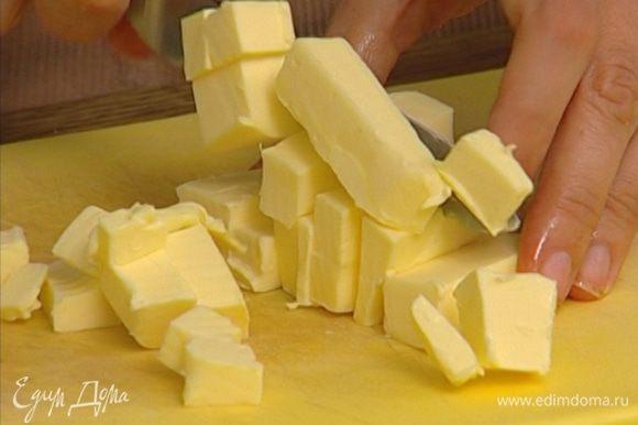 Предварительно охлажденное сливочное масло порезать маленькими кусочками.