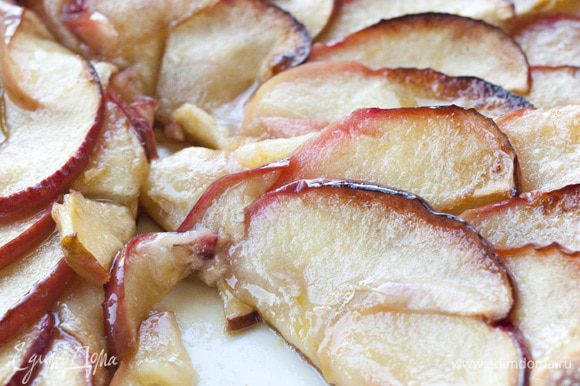 Ломтики яблок веером уложить на тесто, сверху разложить оставшееся масло, присыпать оставшимся сахаром и корицей.